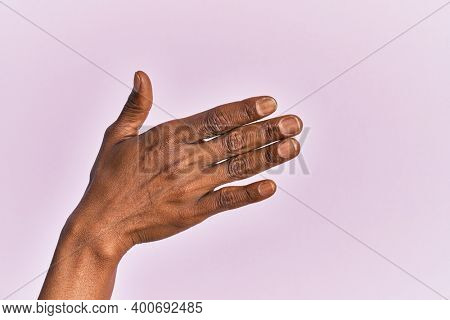 Arm and hand of black middle age woman over pink isolated background presenting with open palm, reaching for support and help, assistance gesture