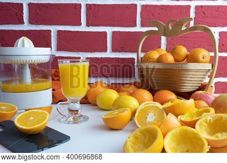 Freshly Squeezed Orange Juice In A Glass, Whole And Squeezed Oranges On The Table, Behind A Brick Wa