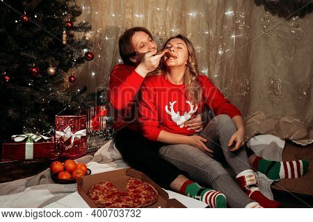 Young Couple Sitting Beside Christmas Tree And Eating Pizza.