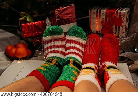 Male And Female Feet In Winter Socks Touching Each Other. Man And Woman Sitting Near A Christmas Tre