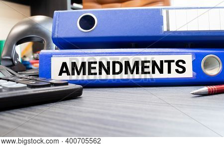 File With Word Amendments Means Settlement In Front Of A Businesswoman Sitting Behind Her Desk In Of