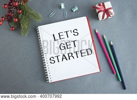 Let's Get Started Word On White Ring Binder Notebook With Hand Holding Pencil On Wood Table,business