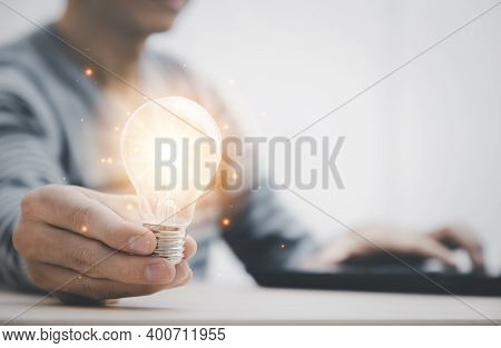 Businessman Hand Holding Light Bulb And Working With Computer On The Desk, Saving Energy And Money,t