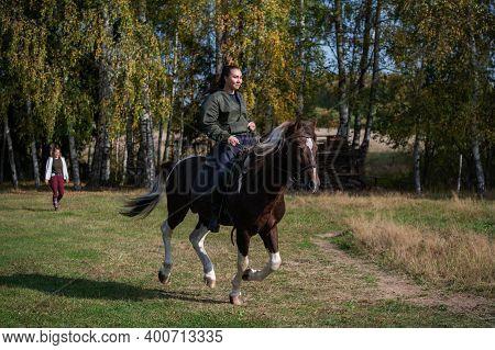 Cute Girl Equestrian Instructor Rides A Horse In An Equestrian Club.