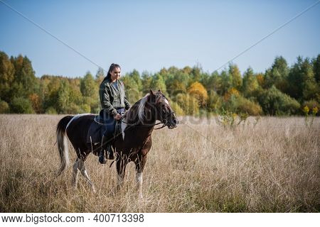 A Pretty Girl Came To The Country Equestrian Club And Rides A Horse Through The Fields In The Fall.
