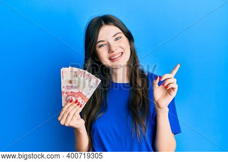 Young beautiful caucasian girl holding 10 colombian pesos banknotes smiling happy pointing with hand and finger to the side
