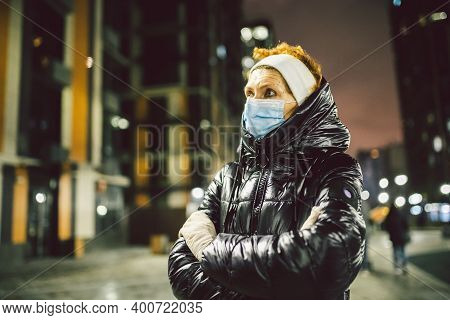 Senior Caucasian Red Hair Woman Medical Protective Mask On Her Face And White Gloves During The Coro