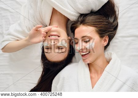 Two Young Gorgeous Smiling Women With Dark Hair In White Bathrobes Lying In Bed With Cosmetic Mask O