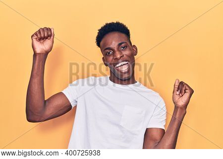 Young african american man wearing casual clothes dancing happy and cheerful, smiling moving casual and confident listening to music