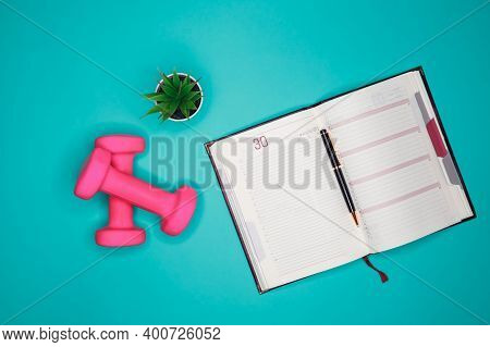 Workout Plan In Notebook. Flat Lay Of Calendar Plan With Pink Dumbbell, Sport Equipments, Fitness It