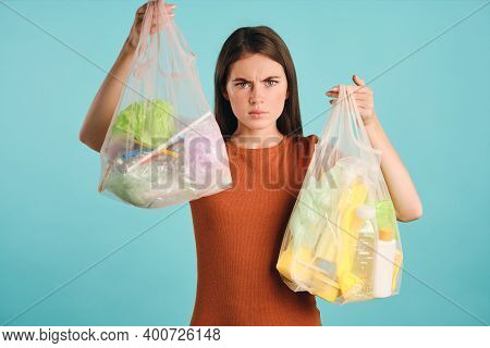 Angry Girl In T-shirt Holding Eco Bags With Plastic Waste Wrathfully Looking In Camera Over Colorful