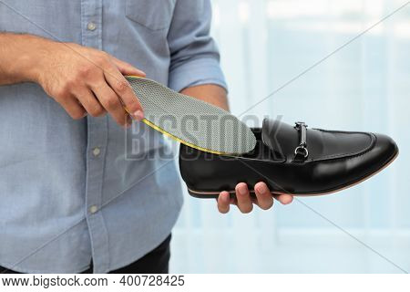 Man Putting Orthopedic Insole Into Shoe Indoors, Closeup. Foot Care