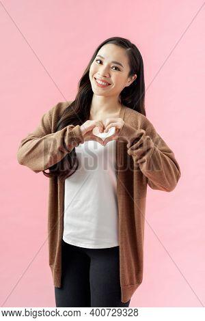 Young Woman Standing Isolated On Pink Background Showing Heart Shape Hand Gesture Looking Camera Smi