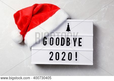 Lightbox With Text Bye Bye 2020! And Santa Hat On Light Grey Background, Flat Lay