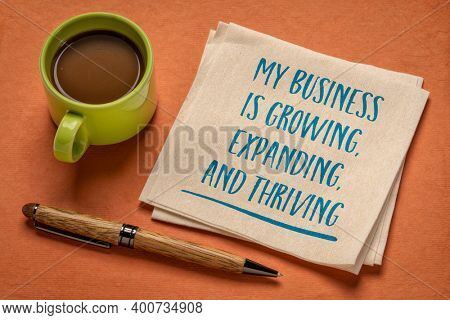 my business is growing, expanding, and thriving - handwriting on a napkin with a cup of coffee, positive affirmation for business owners