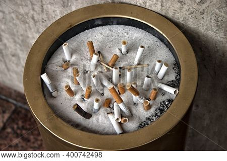 Close-up Of An Ashtray With Cigarette Butts Standing At The Entrance To The Hotel.