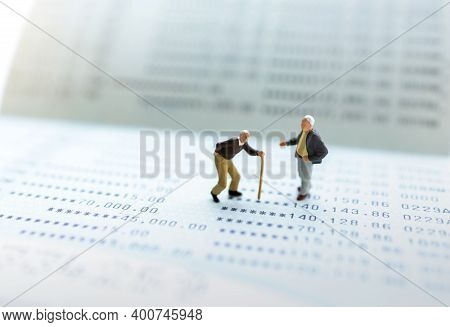 Miniature People Stand On The Bank Passbook, Retirement Planning And Life Insurance Concepts.