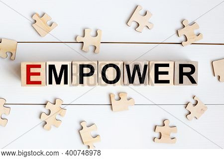 The Word Empower Written In A Wooden Cube Near Wooden Puzzles