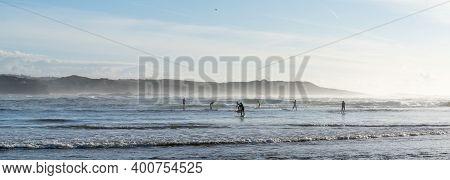 Vila Nova De Milfontes, Portugal: 23 December 2020: Group Of Surfers Enjoy Catching Wves On Sup Padd