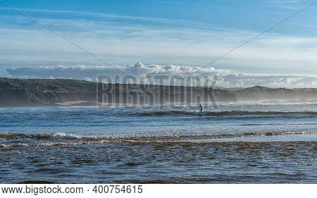 Vila Nova De Milfontes, Portugal: 23 December 2020: Surfer Enjoys Catching Waves On A Sup Paddleboar
