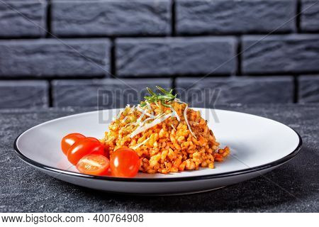 A Portion Of Ground Beef Risotto Bolognese Sprinkled With Grated Parmesan Cheese On A Plate With A B