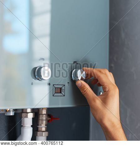 Close-up Of Male Hand Adjusting Temperature Of Water Heater. Modern Home Gas Fired Boiler.