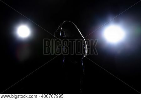 Silhouette Of Sad Woman Isolated On Dark Background In Lanterns Light