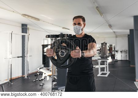 Man Working Out Wearing Face Mask In The Gym,covid-19 Pandemic Social Distancing Rules While Working