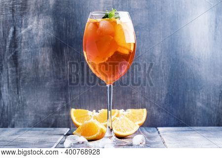 Summer Cocktail Aperitif With Orange Bitter, Fruit, Ice And Soda In Tall Glass, Gray-silver Backgrou