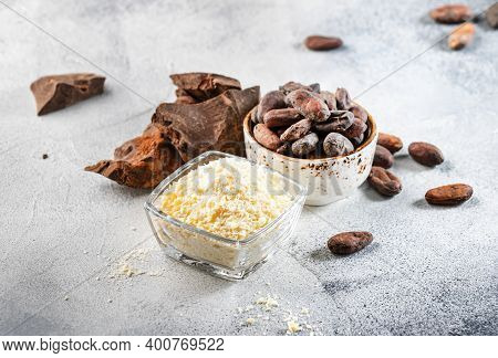 Organic Cocoa Butter, Cocoa Beans, Grated Cocoa Lump, Dark Chocolate On Gray Blue Background. Copy S