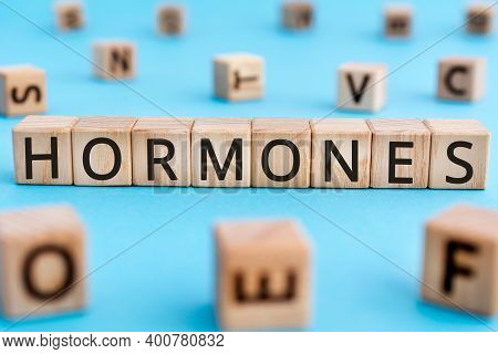 Hormones - Word From Wooden Blocks With Letters, Hormones Concept, Random Letters Around Blue Backgr