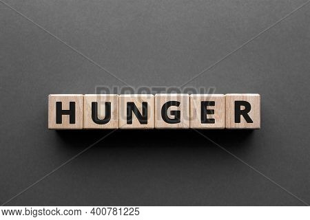 Hunger - Words From Wooden Blocks With Letters, Need To Eat Hunger Concept, Top View Gray Background