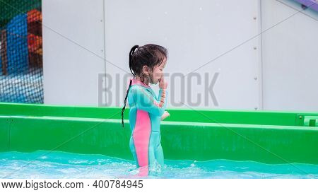 Child Is Rubbing Water On His Face After Getting Out Of Pool. Children Play With Water In Summer. Ki