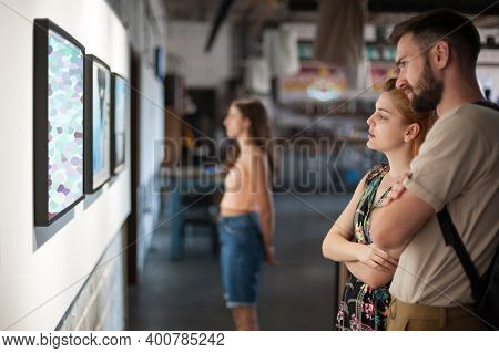 Group Of Friends In Modern Art Exhibition Gallery Hall Contemplating Artwork. Abstract Painting