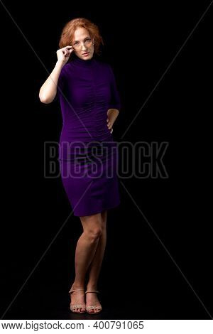 Young Woman Looking Strictly Over Her Glasses. Woman Teacher Wearing Glasses And Purple Casual Dress