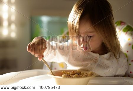 Two Years Old Eats Porridge By Herself With A Spoon. Child Development Concept
