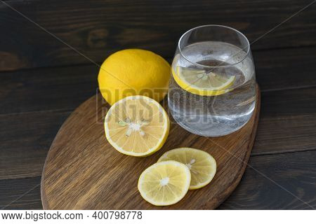 Cutted Lemon, Whole Lemon And Transparent Glass With Pure Water With Lemon Slice In It  Are On Woode