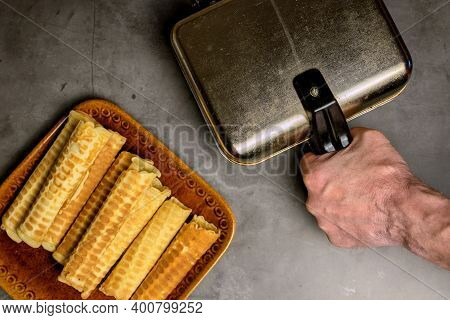 Cooking Waffles At Home - A Waffle Iron, A Mans Hand Holding A Pen. Ready-made Waffles On A Plate. C