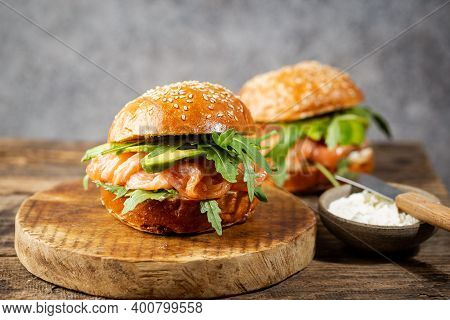 Burger Sandwich With Salmon, Cream Cheese, Avocado And Arugula On A Light Background, Concept Diet F