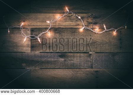 A Strand Of Lit White Lights On An Aged Barn Wood Wall.