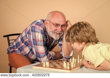 Playing Chess. Kid Playing Chess With Grandpa. Grandfather And Grandson Play Chess. Family Activitie