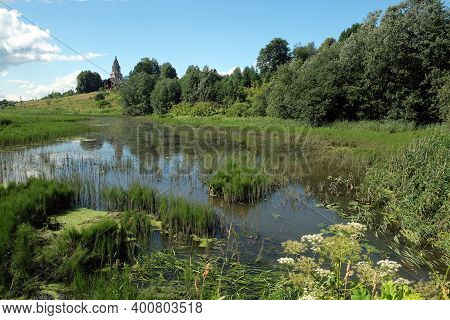 Beautiful Hush Rural Landscape With Still Pond On The Foreground, Old Church At Far And Clouds On Th