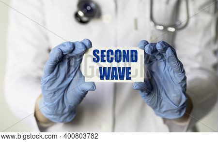 Second Wave Text On White Card. Warning Sign In Doctor's Hand. Second Wave Of Covid-19 Virus. Health