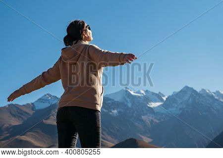 Professional Hiker In Sportswear Stands On Hilltop Against Brown Mountains With Snowy Peaks Lit By B
