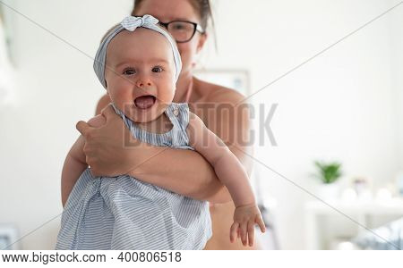 Young Mother Holding Laughing Baby Girl. Bright Lifestyle Background