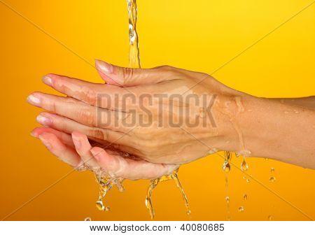 Washing hands on orange background close-up