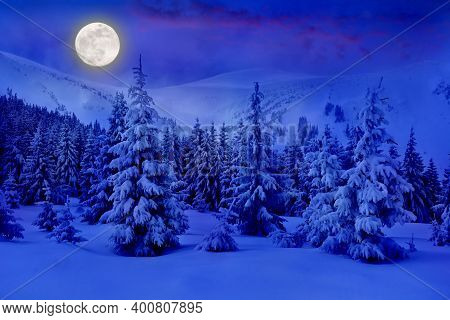 Full Moon Rising Above The Winter Fir Forest Covered Of Snow In Mountains. Christmas Night. Landscap