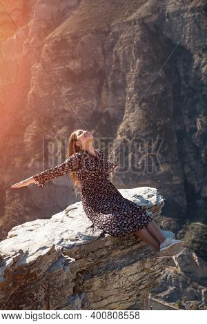 Excited Lady With Long Loose Flowing Hair Sits Smiling On Dangerous Grey Rock Hilltop Edge Against S