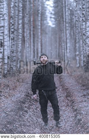 Portrait Of A A Bearded Man With An Axe At The Late Autumn Or Winter Birch Forest. Unfriendly Strang