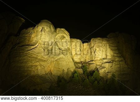 The Four Presidents On Mount Rushmore Are Illuminated With Floodlights Against A Black Sky At Night